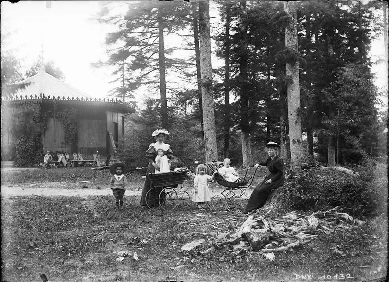 Femmes, enfants et landaus près d'un pavillon forestier