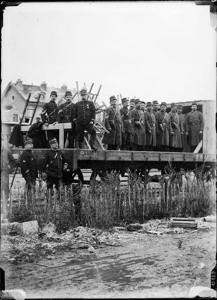Portrait de groupe : militaires sur un bogie, la gare en arrière-plan