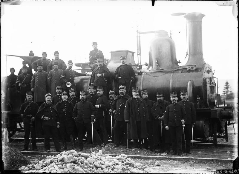 Portrait de groupe : militaires devant une locomotive