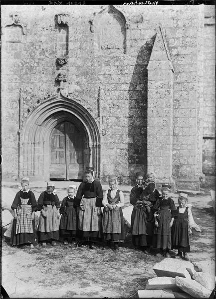 Portrait collectif : groupe de Bretonnes en sabots et costume traditionnel devant le porche de la façade ouest