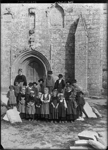 Portrait collectif : groupe de Bretons et Bretonnes en sabots et costume traditionnel devant le porche de la façade ouest