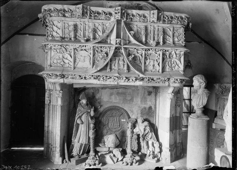 Cheminée gothique, chenets, statue d'évêque et buste de style romain