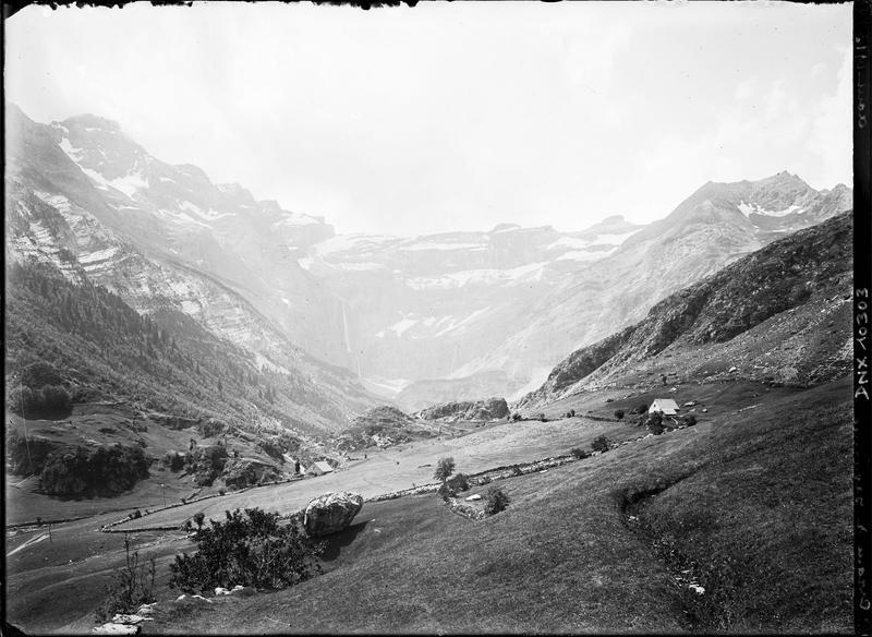 Paysage de montagne : vue générale du cirque, champs et murets de pierre au premier plan