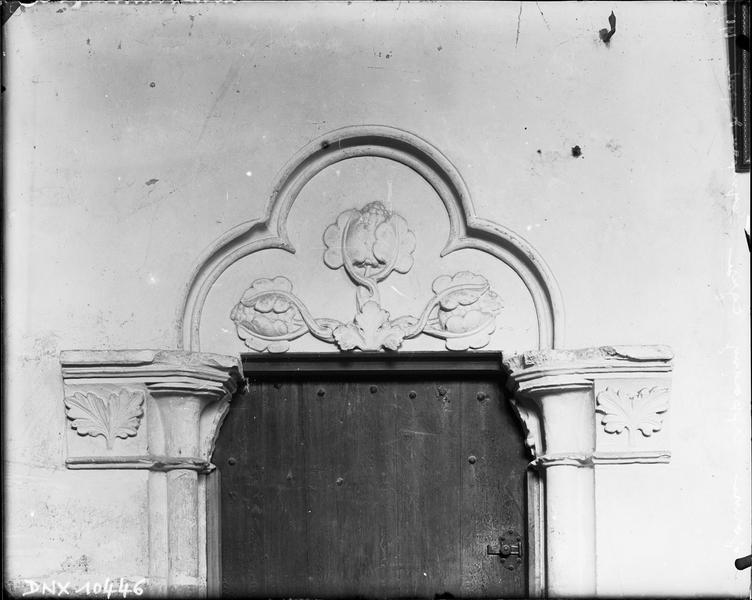Intérieur : tympan de porte sculpté d'un motif végétal dans une chapelle latérale