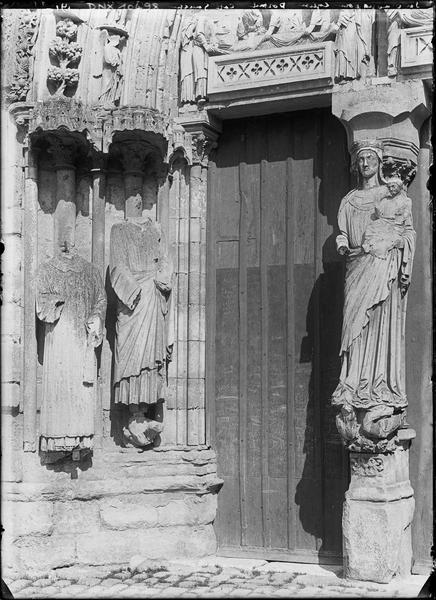 Façade ouest, portail principal, côté gauche : Vierge à l'Enfant au trumeau et piédroit orné de deux statues acéphales