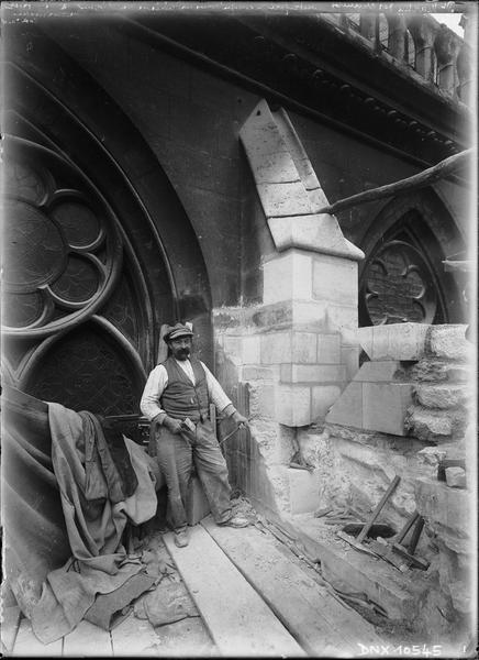 Ouvrier dégageant un contrefort dans la liaison du clocher à hauteur de corniche côté ouest