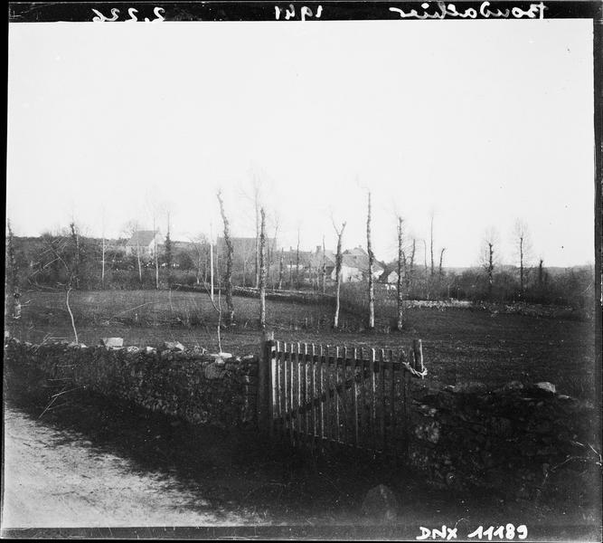 Paysage rural : muret en pierres, barrière, arbres et maison à l'arrière-plan