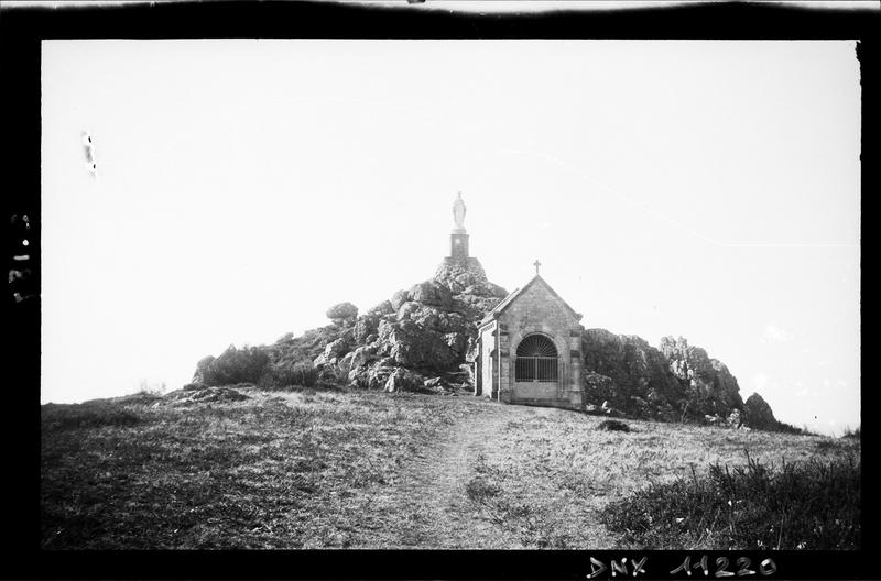Façade, au pied d'une butte rocheuse surmontée d'une Vierge monumentale