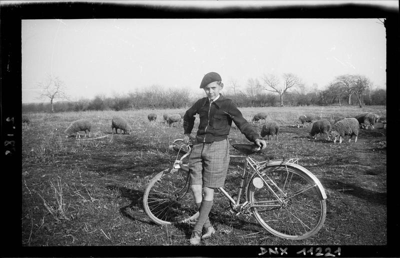 Jeune garçon appuyé à une bicyclette