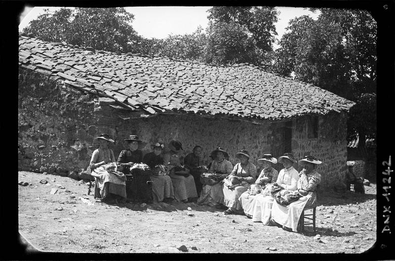Portrait collectif : groupe de dentellières assises, coiffées de grands chapeaux et portant leurs fuseaux sur les genoux