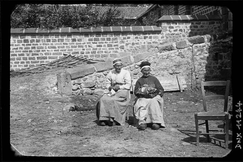 Dentellières assises, chaussées de sabots et portant leurs fuseaux sur les genoux