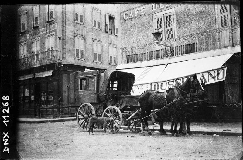 Voiture à cheval devant la façade d'un café
