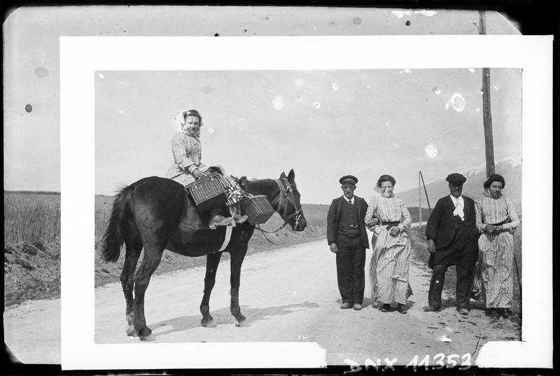 Femme montant un cheval en amazone, et groupe de villageois
