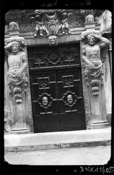 Porte monumentale flanquée d'atlantes et ornée de putti encadrant un blason