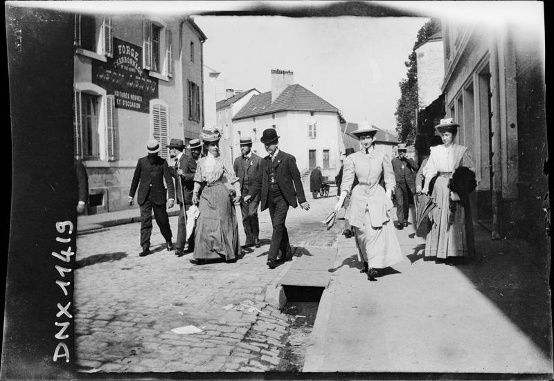 Passants devant une enseigne : « Forge et Charronnage, Léon Leduc, Voitures neuves et d'occasion »