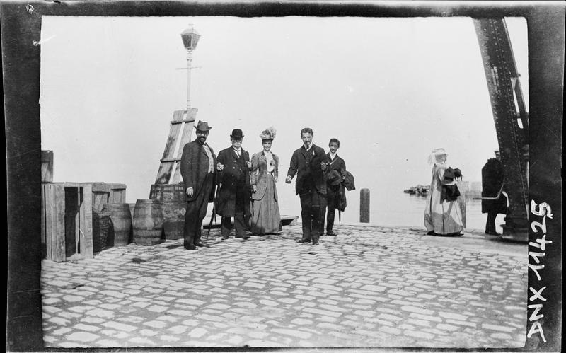 Portrait collectif sur un quai, tonneaux et caisses à l'arrière-plan