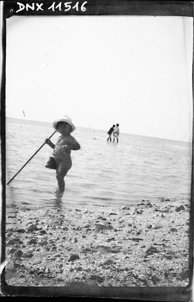 Scène de plage : enfant en maillot de bain à rayures