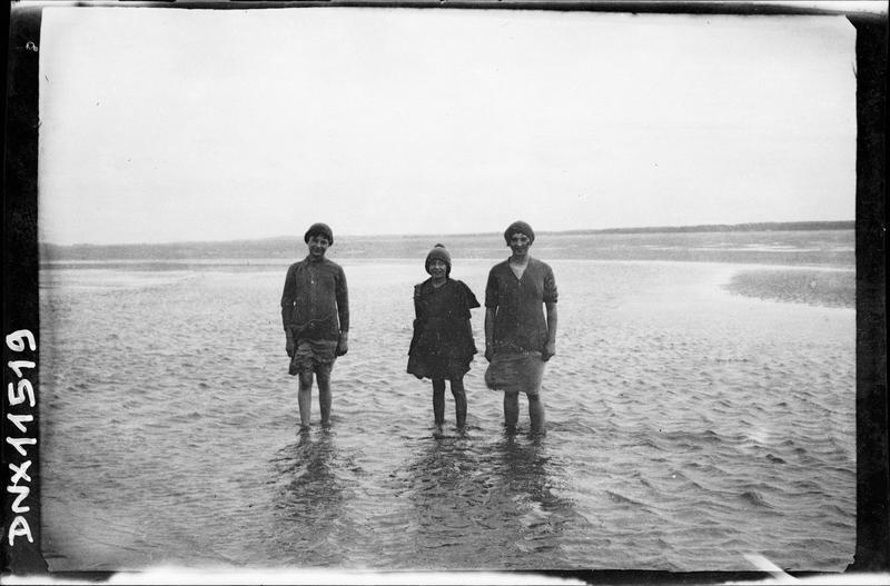 Scène de plage : trois personnes les pieds dans l'eau