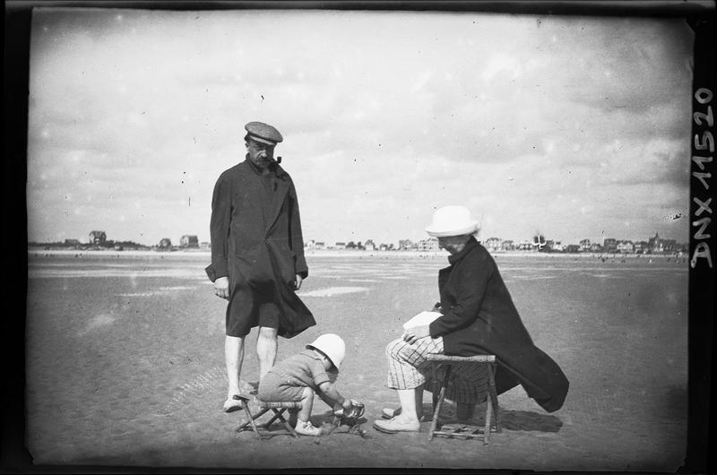 Scène de plage : homme à la pipe, femme et enfant assis sur des pliants