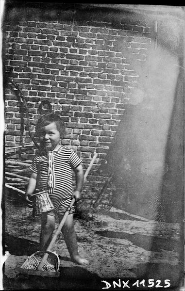 Enfant à l'épuisette, en maillot de bain à rayures