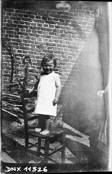 Petite fille debout sur une chaise