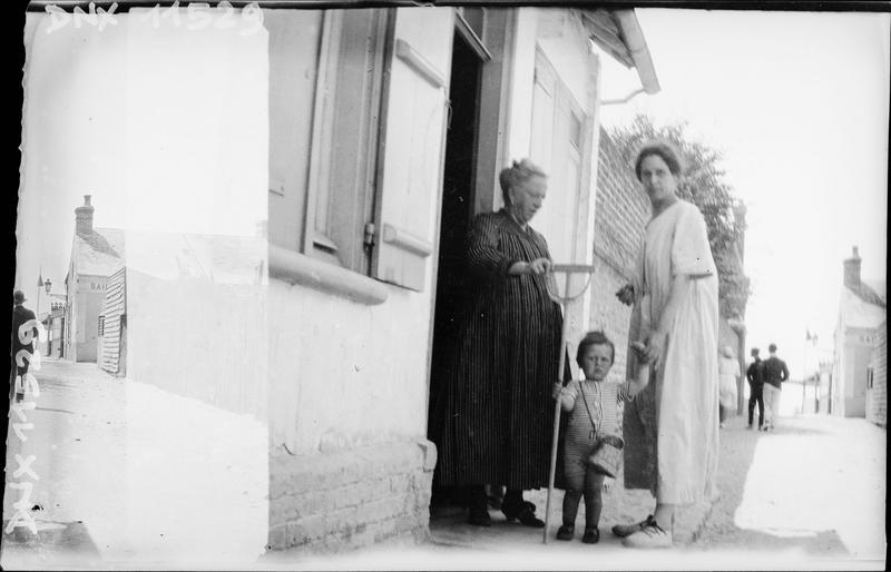 Enfant à l'épuisette entre deux femmes, sur le palier d'une maison