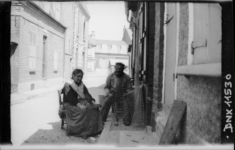 Vieille femme assise et pêcheur réparant ses filets, dans une ruelle