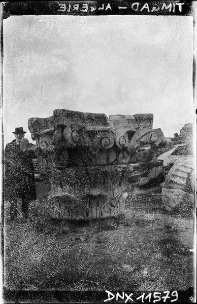 Personnage debout à côté d'un chapiteau corinthien monumental