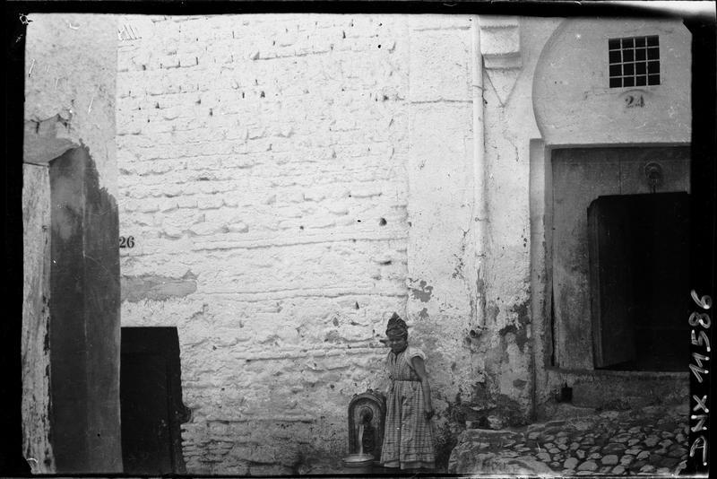 Femme à côté d'une fontaine