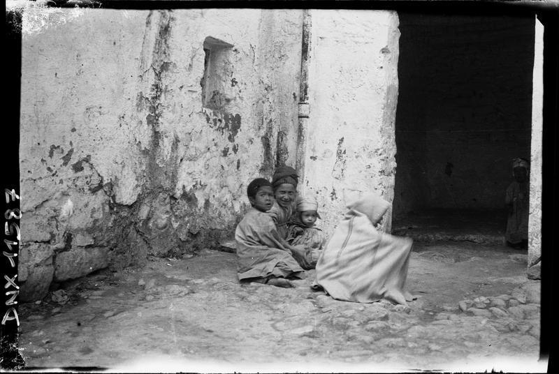 Femme et enfants accroupis au pied d'un mur