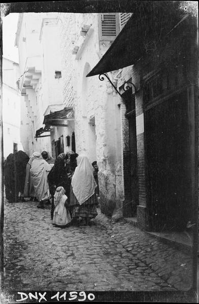 Quartier arabe : une rue animée, femmes et enfants vus de dos
