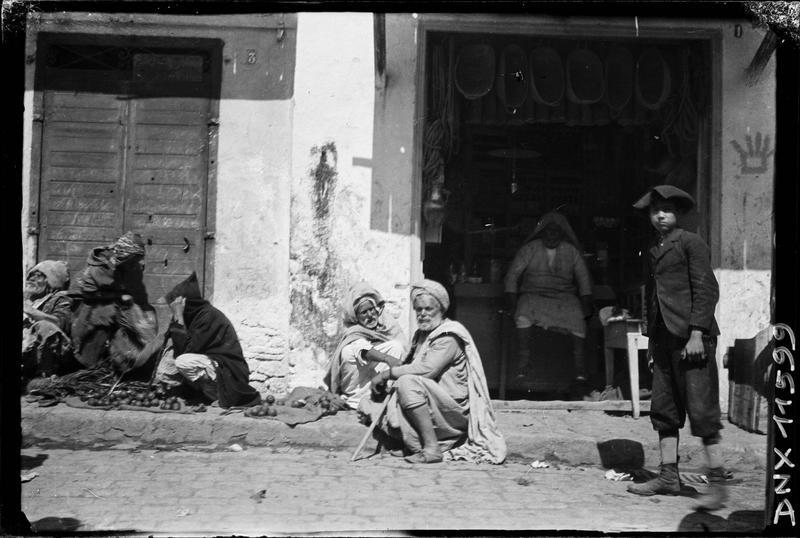 Quartier arabe : personnages accroupis devant une échoppe