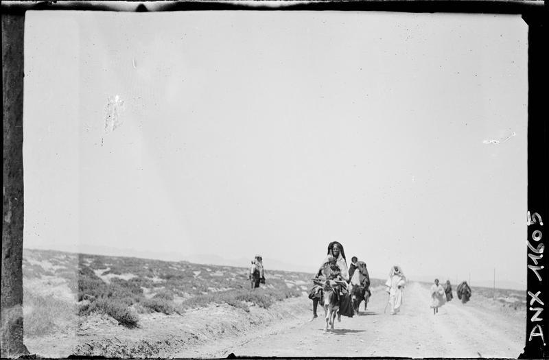Passants sur une route, cheminant à pied et à dos d'âne