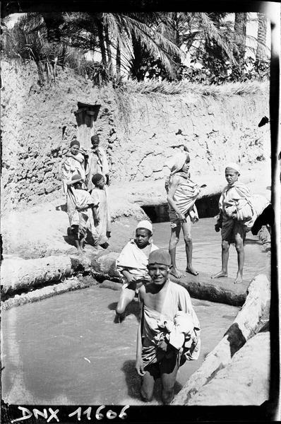 Dans la palmeraie : enfants se baignant dans une source
