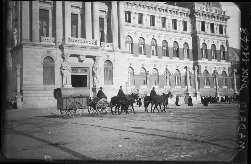 Charrette bâchée tractée par un attelage d'ânes, devant la façade d'un édifice