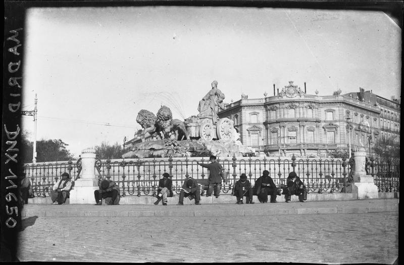 Hommes assis au pied des grilles qui entourent la fontaine, palais en arrière-plan