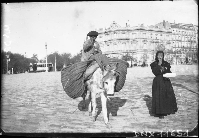 Scène de rue : âne portant des paniers, femme cheminant à ses côtés, palais en arrière-plan