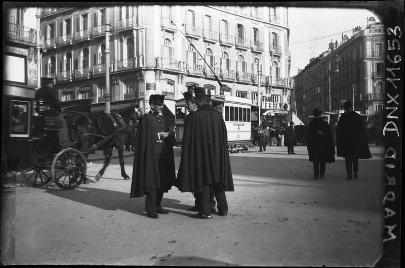 Scène de rue : conciliabule d'hommes en uniforme, véhicule tiré par un cheval, tramway à l'arrière-plan