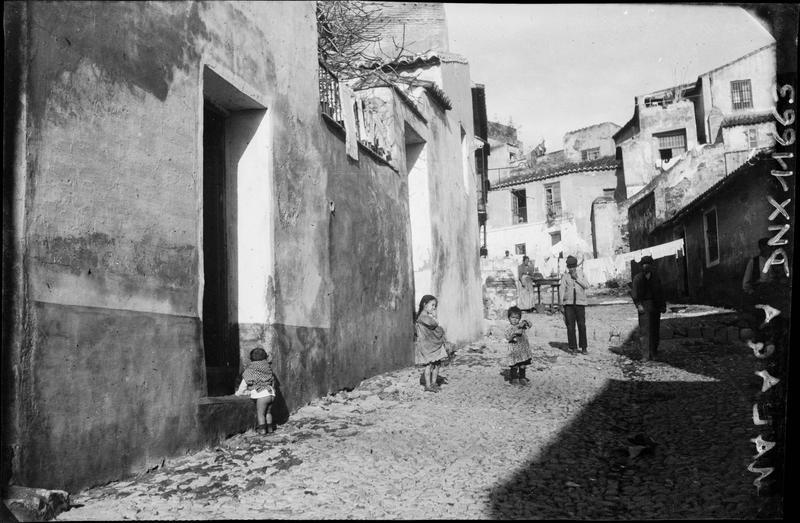 Enfants et personnages dans une rue de la vieille ville, linge séchant sur une corde