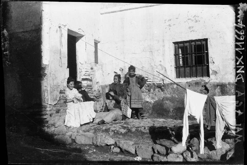 Femmes assises sur le seuil d'une vieille maison, linge séchant sur une corde
