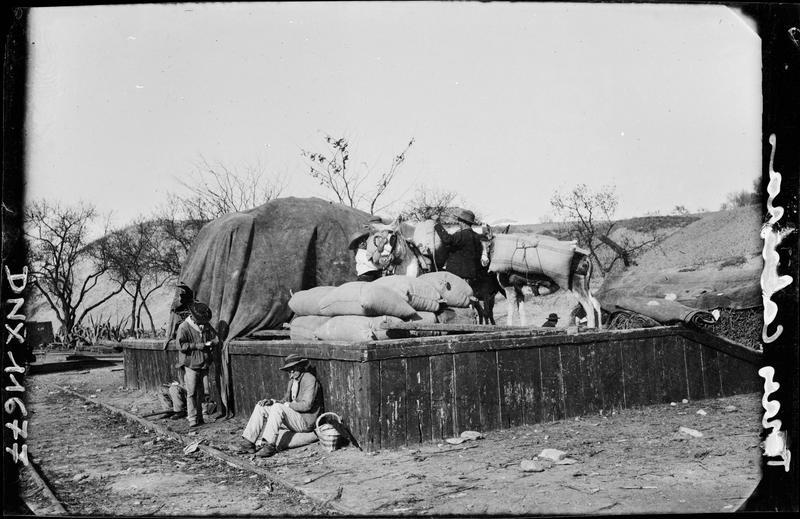 Au bord d'une voie ferrée : chargement de sacs à dos d'âne