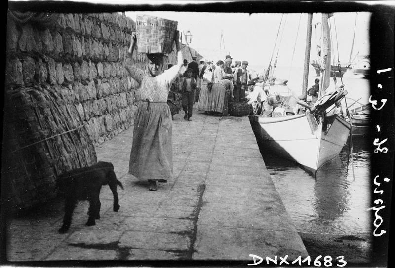 Barque à quai : déchargement de marchandises, femme portant un panier sur la tête