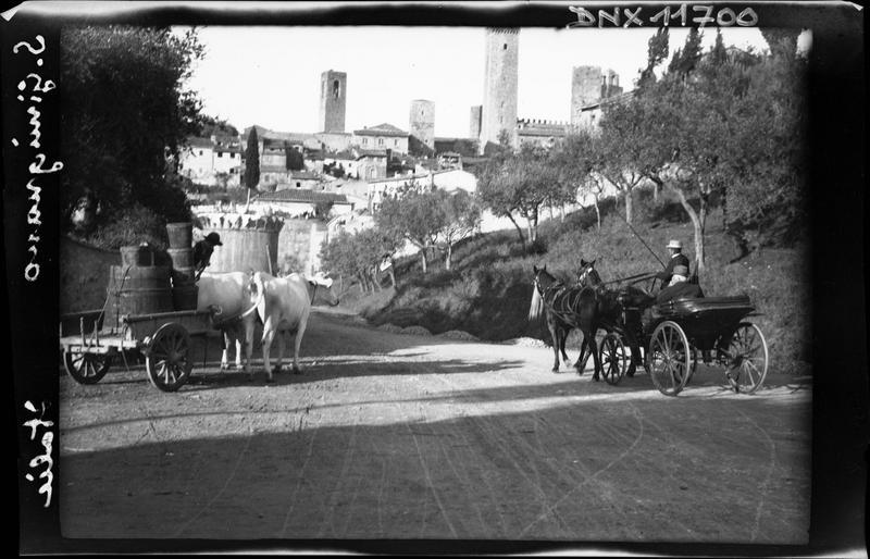 Calèche et charrette tirée par des boeufs à l'entrée de la ville