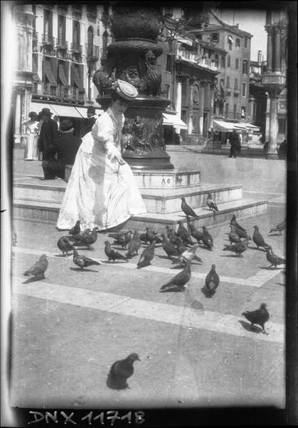 Femme nourrissant des pigeons au pied d'une colonne, près de la basilique Saint-Marc