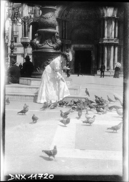 Femme nourrissant des pigeons au pied d'une colonne, devant l'entrée de la basilique