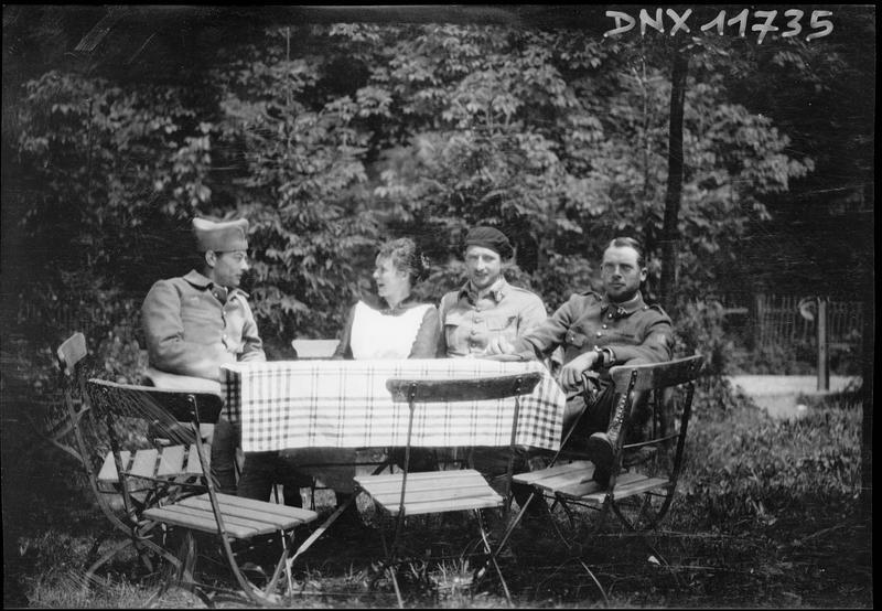 Portrait collectif : trois militaires et une femme assis à une table