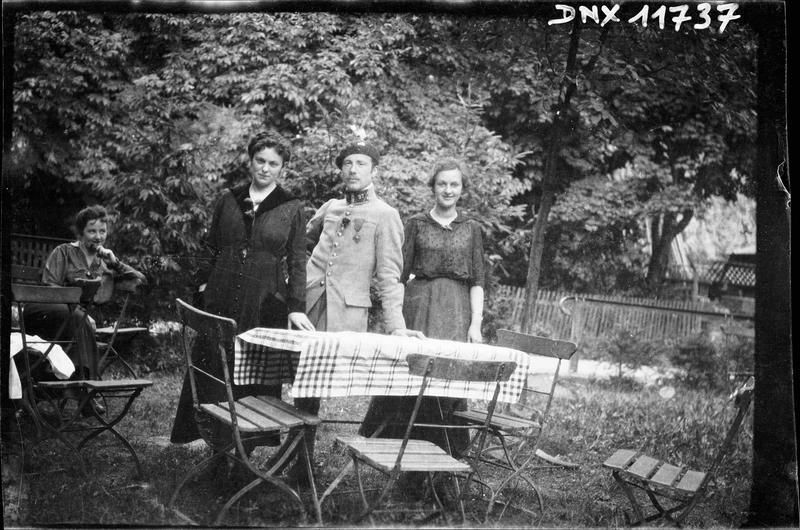 Portrait collectif : un militaire et deux femmes debout derrière une table