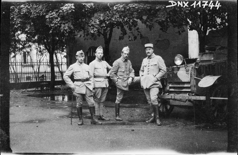Portrait collectif : trois militaires et un officier devant un camion