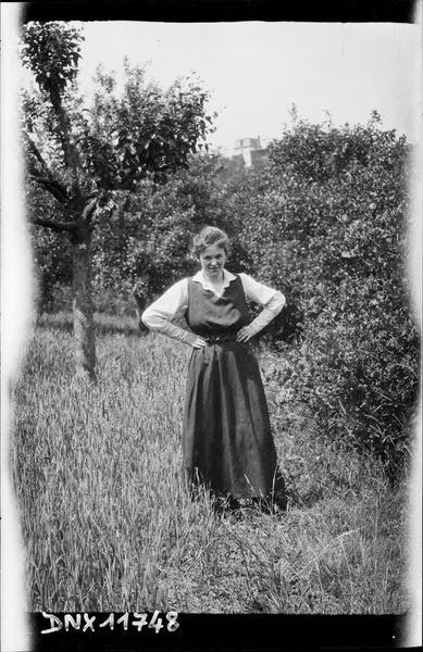 Portrait : jeune femme debout, les mains aux hanches
