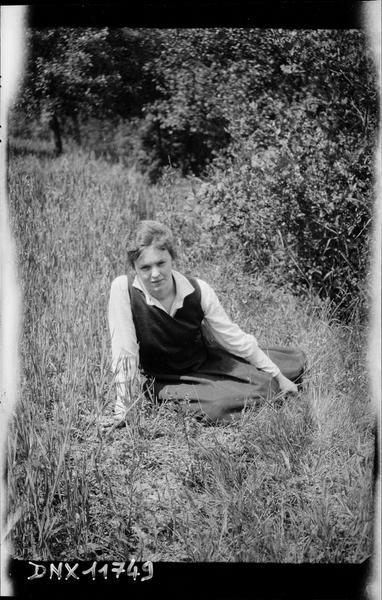 Portrait : jeune femme assise dans l'herbe